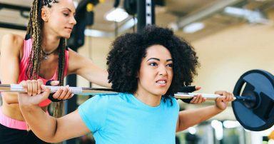A personal trainer helping a client with weight lifting