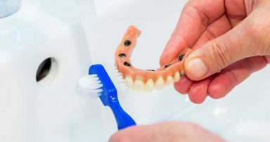 Someone cleaning dentures with a toothbrush