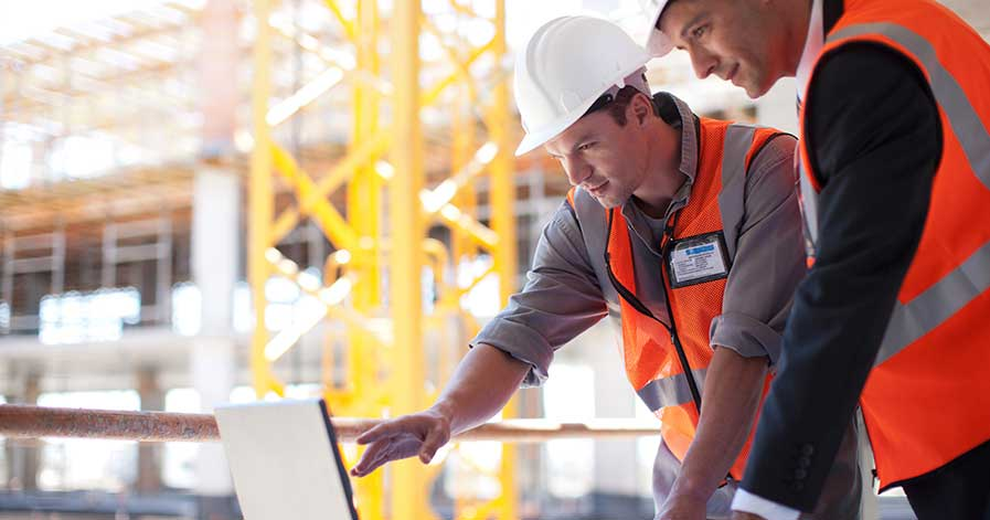 Two construction workers on site, looking at a laptop