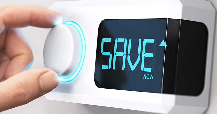 "Someone adjusting a smart thermostat that says ""save now"""