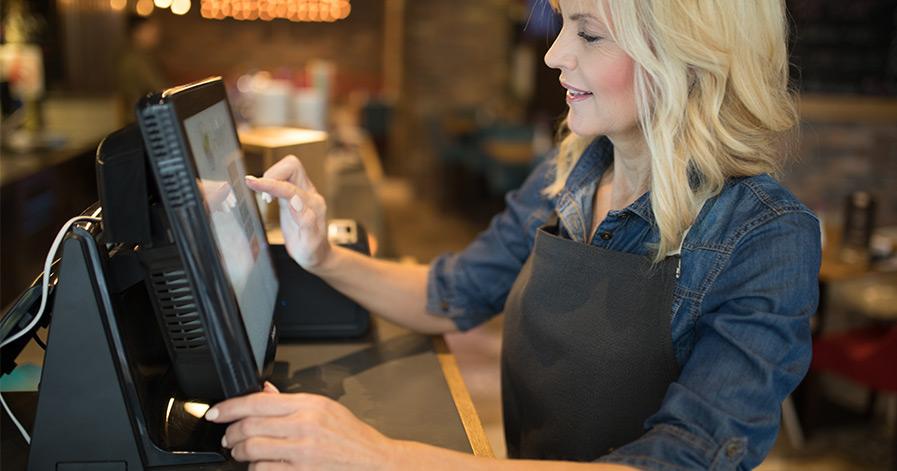 Server punching in order on cash register