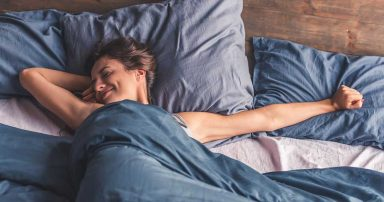 A woman laying in bed under a weighted blanket
