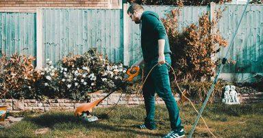 A man using a lawn mower in his backyard