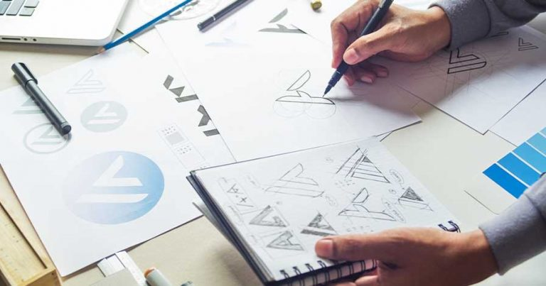 A person drawing logo designs.