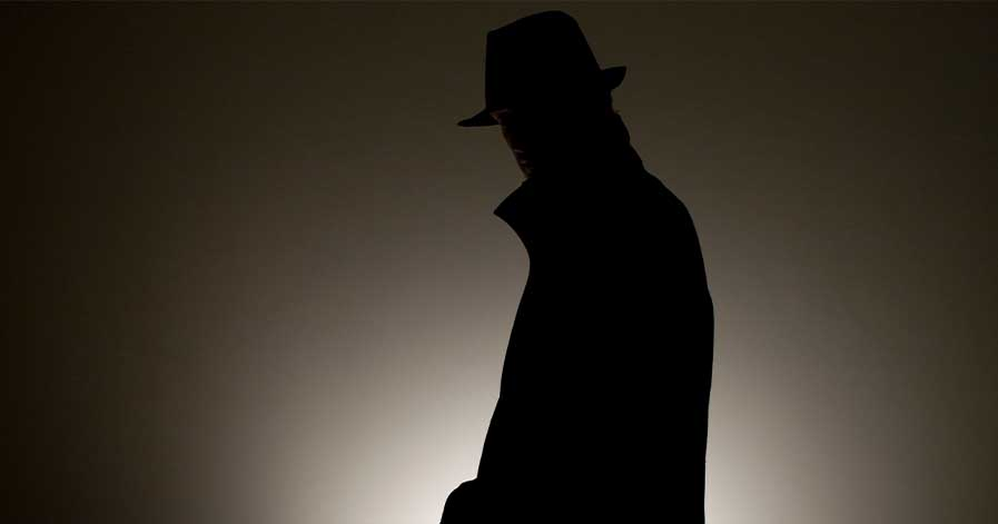 A dark image of a man wearing a jacket and fedora.