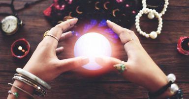An orb between a person's hands. Around the orb is an assortment of bracelets.